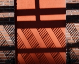 Fire escape shadow on brick wall